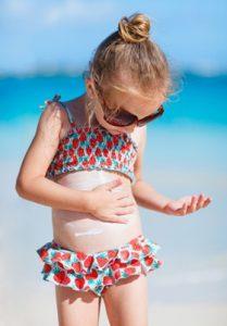 toddler applying sunblock